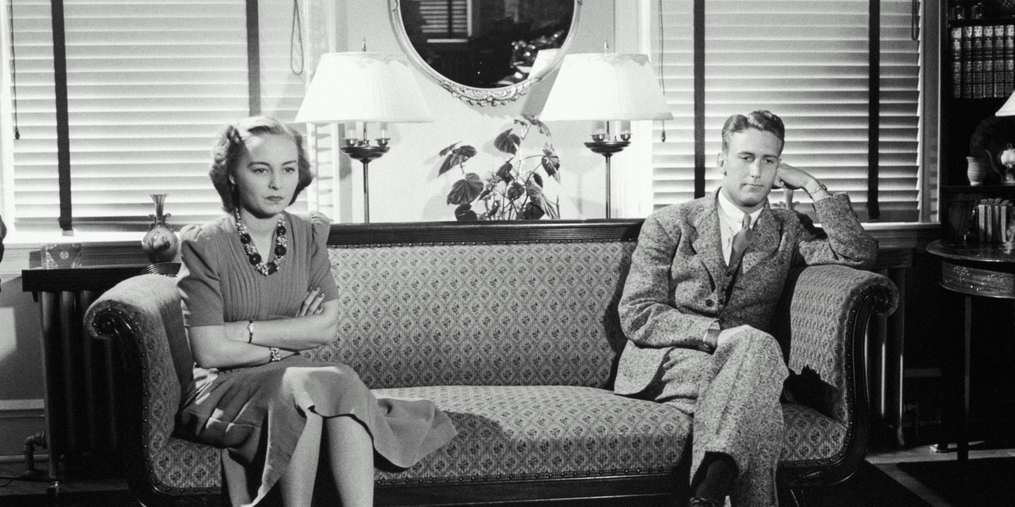 MAN AND WOMAN ON COUCH, OPPOSITE SIDES